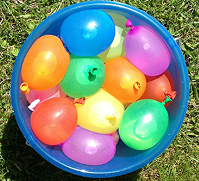 A bucket of colorful water balloons
