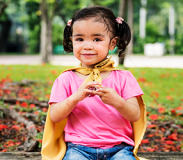 Preschool child in the park participating in a fingerplay song