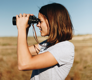 A woman outdoors looking through binoculars