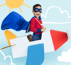A child flying in a cardboard airplane against a crayon drawing of a sunny sky